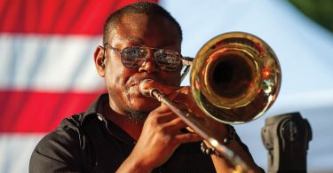 man playing trombone american falg in background