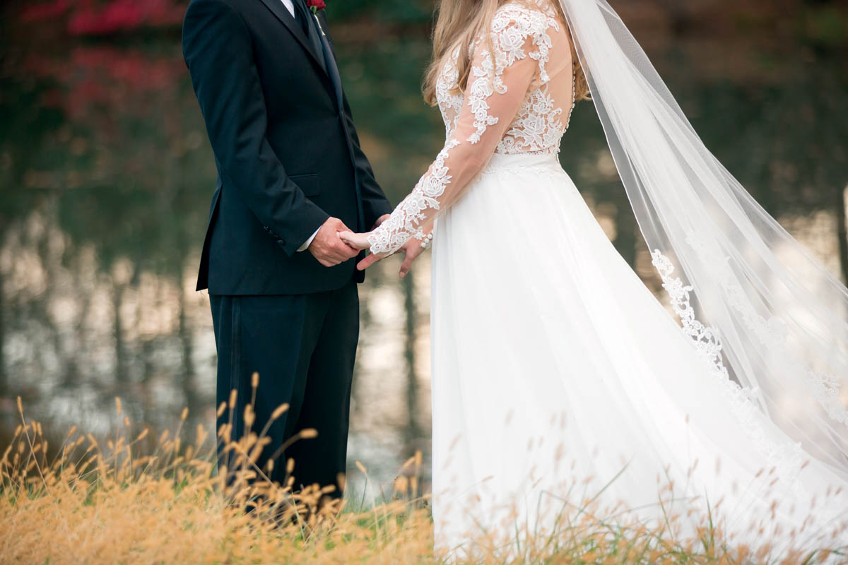wedding day holding hands by a lake