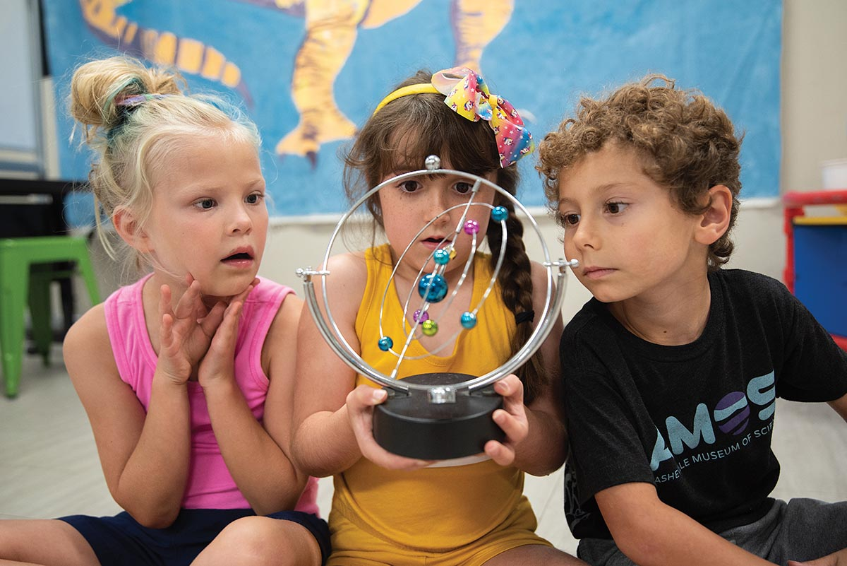 Children looking at a model of the solar system