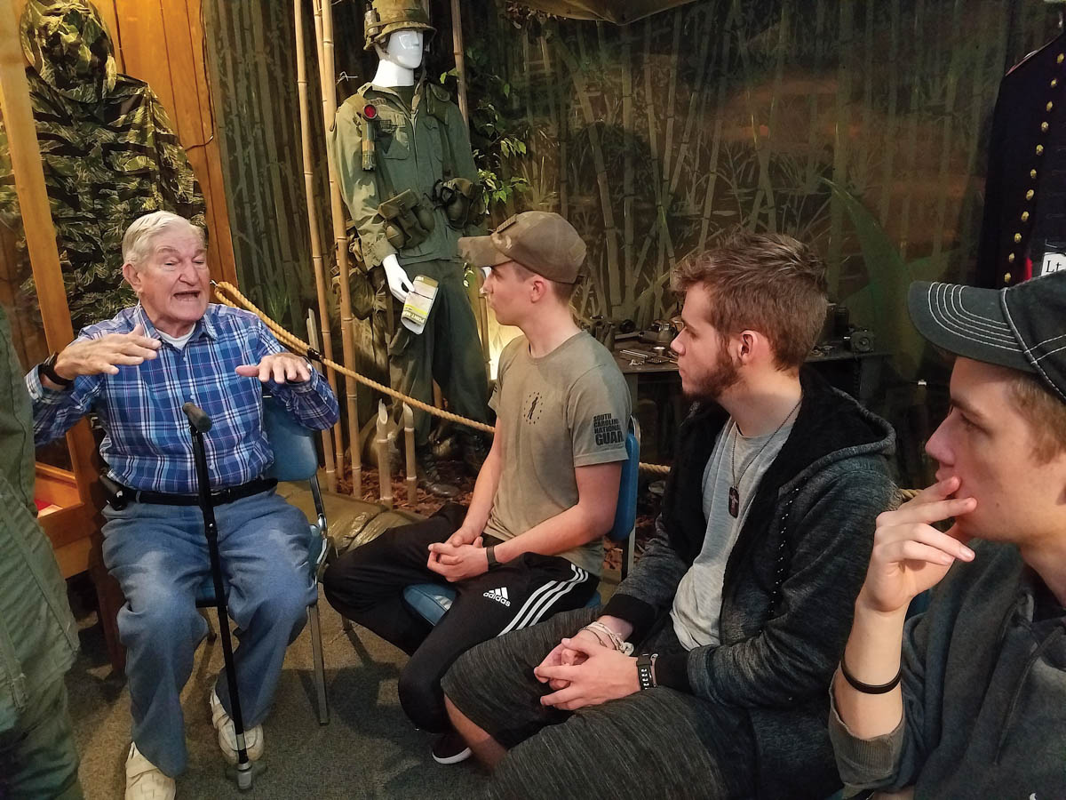 D-Day veteran George Sarros, age 94 tells campers Nathan Flake, Ethan Swords, and Jacob Flake about Normandy invasion. Photo by Janis Allen