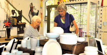 two women looking at pottery