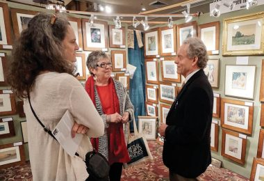 three people conversing with art in the background